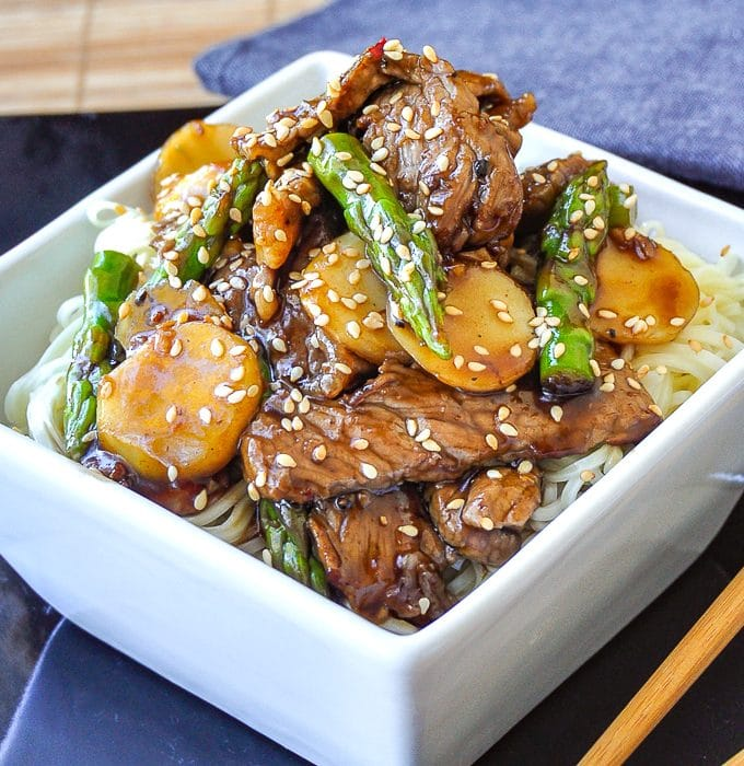 Easy Sesame Beef and Asparagus close up image served on noodles in a white bowl