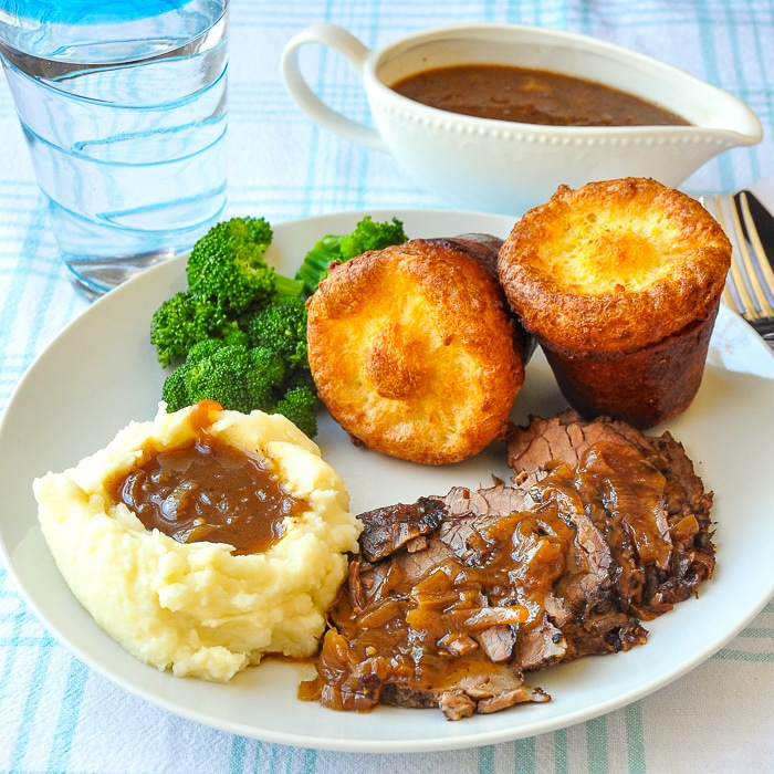 French Onion Braised Beef Brisket with mashed potatoes amd popovers on a white plate