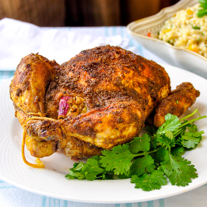 Indian Spiced Roast Chicken pictured on a white plate with fresh coriander leaves