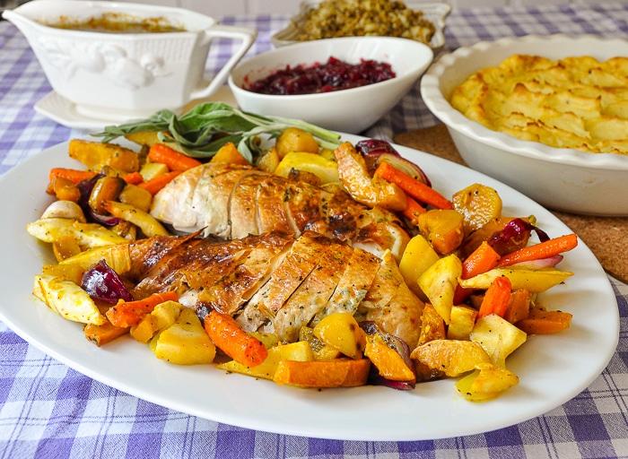 Lemon Sage Butter Roast Turkey wide shot photo of turkey and maple roasted vegetables on a white serving platter.