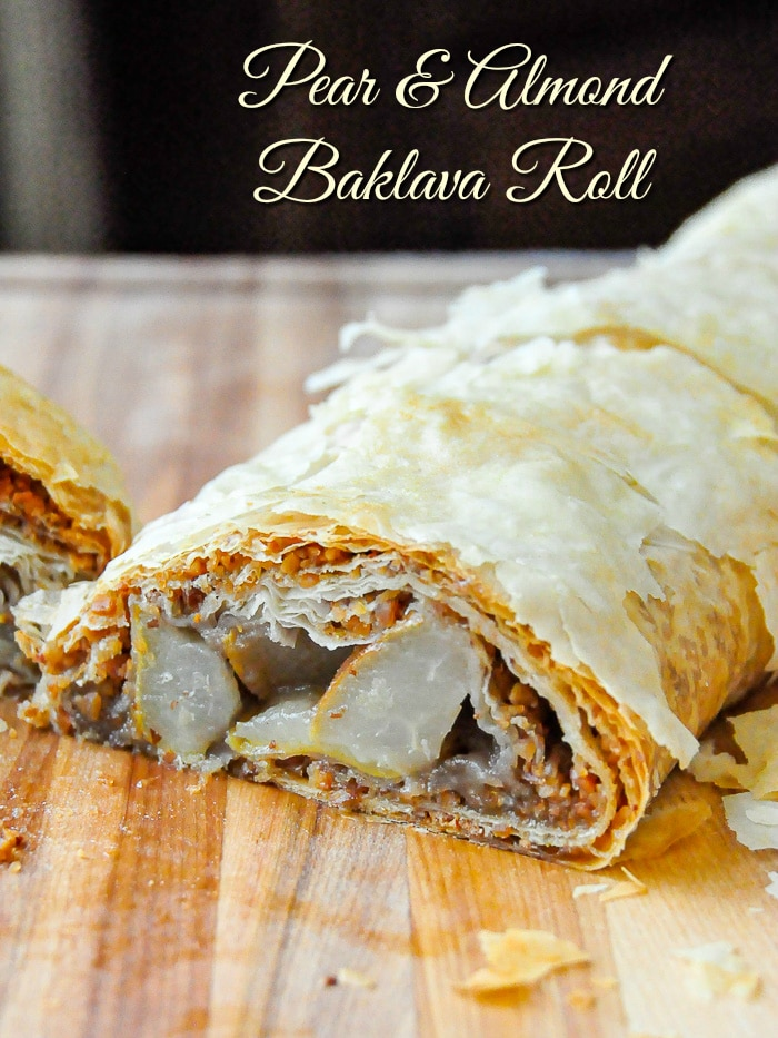 Pear Almond Baklava Roll photo of full roll on a wooden cutting board with title text added for Pinterest