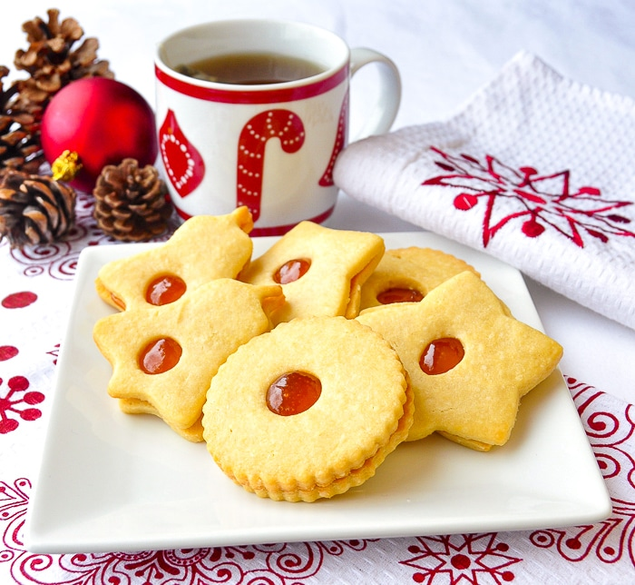 Apricot Almond Jammie Dodgers on a white plate with a cup of tea and christmas decorations in the background