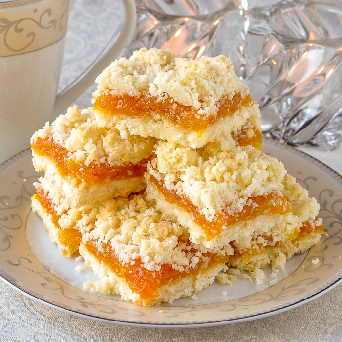 Apricot Coconut Crumble Bars on a serving plate with tea and votive candles in background