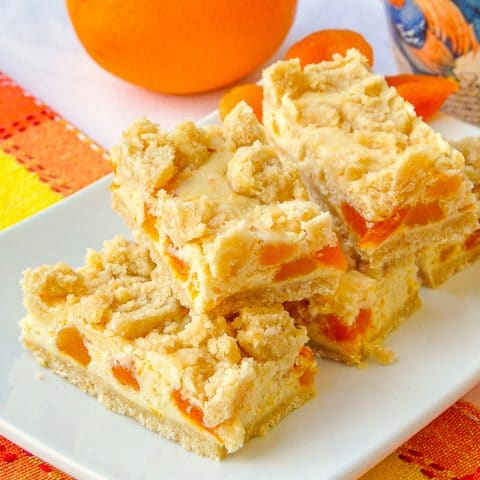 Apricot Orange Cheesecake Bars close up photo of the cookie bars stacked with oranges and apricots in background
