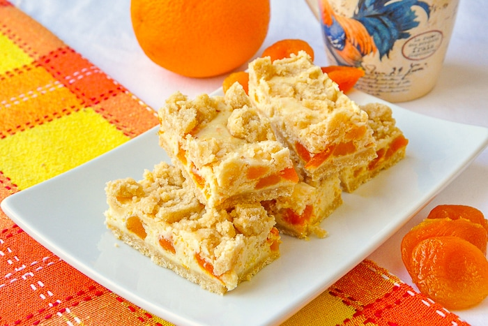 Apricot Orange Cheesecake Bars wide shot photo of the cookie bars stacked on a white platter