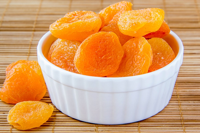 Dried apricots for Apricot Coconut Cookie Bars shown in white ramekin.