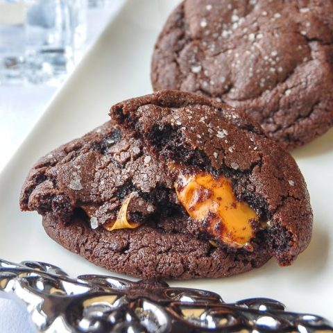 Caramel Stuffed Salted Chocolate Cookies photo of a cookie broken open to reveal the caramel centre