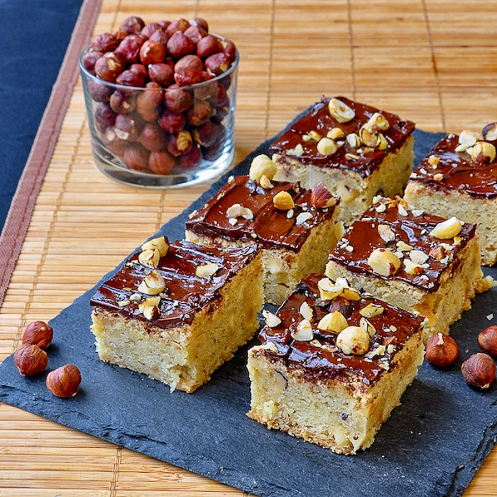 Chewy Hazelnut Bars shown on slate tray with roasted hazelnuts in background