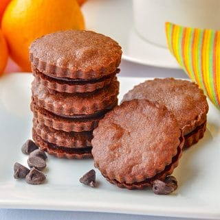 Chocolate Orange Shortbread Sandwich Cookies on white serving plate with oranges in background