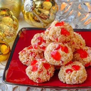 Easy Cherry Almond Macaroons shown on red serving plate with Christmas decorations in background