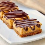 Gingersnap Pumpkin Cheesecake Bars close up photo of bars on a white platter