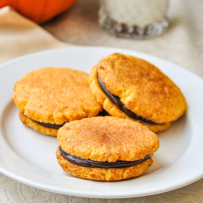 Pumpkin Spice Cookies with chocolate filling on a white plate with glass of milk
