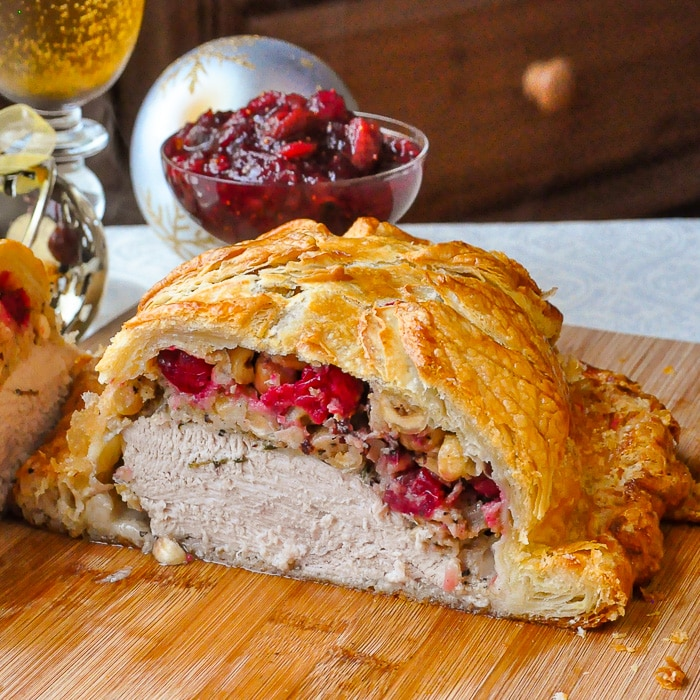Cranberry Hazelnut Turkey Wellington close up photo of wellington cut open to reveal stuffing and turkey inside
