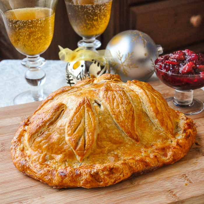Cranberry Hazelnut Turkey Wellington shown uncut on a wooden cutting board