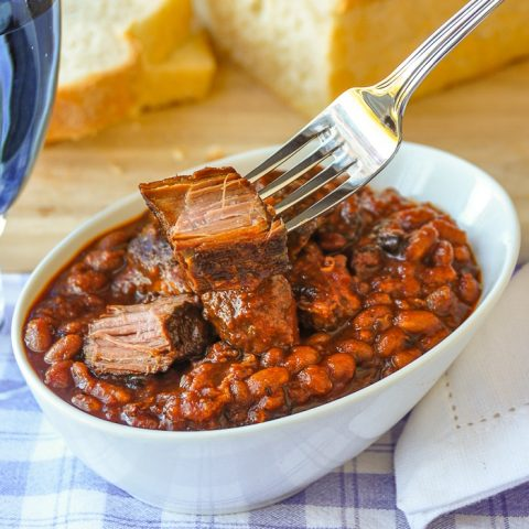 Maple Chipotle Pulled Pork and Beans. in a white bowl with fork holding a chunk of pulled pork.