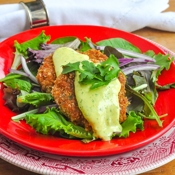 Shrimp Cakes with lime aioli photo ahown on a red plate with salad