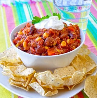 Quinoa Vegetarian Chili image of single serving with tortilla chips in a white bowl.