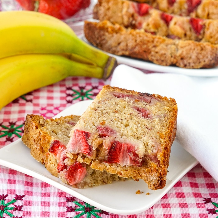 Strawberry Banana Bread close up photo of cut slice on a small white plate