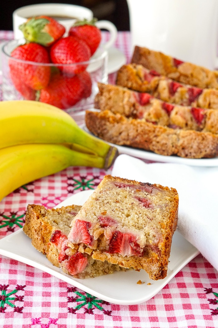 Strawberry Banana Bread photo of a single slice on white plate with coffee, bananas and strawberries in background