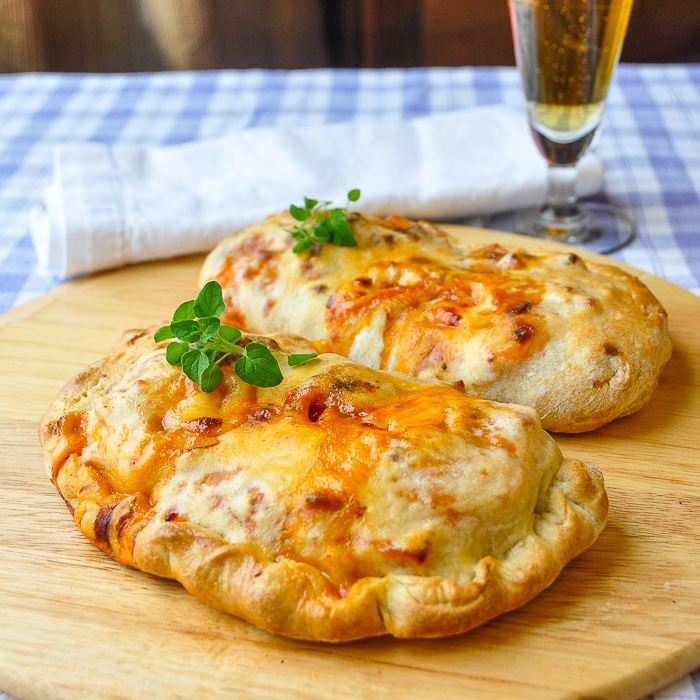 Crispy Thin Crust Barbecue Chicken Pizza made as calzones on a wooden peel