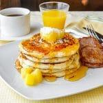 Pina Colada Pancakes on white plate with sausage patties