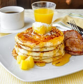 Pina Colada Pancakes on white plate with sausage patties
