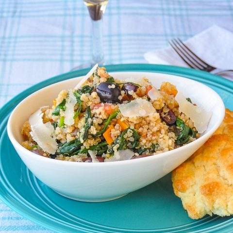 Spinach Parmesan Quinoa in a white bowl with biscuit on the side