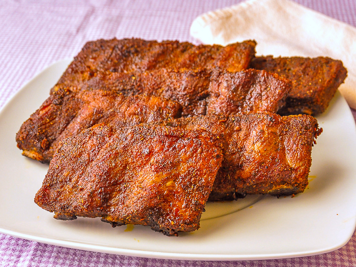 Uncut Dry Rubbed Oven Ribs on a white platter