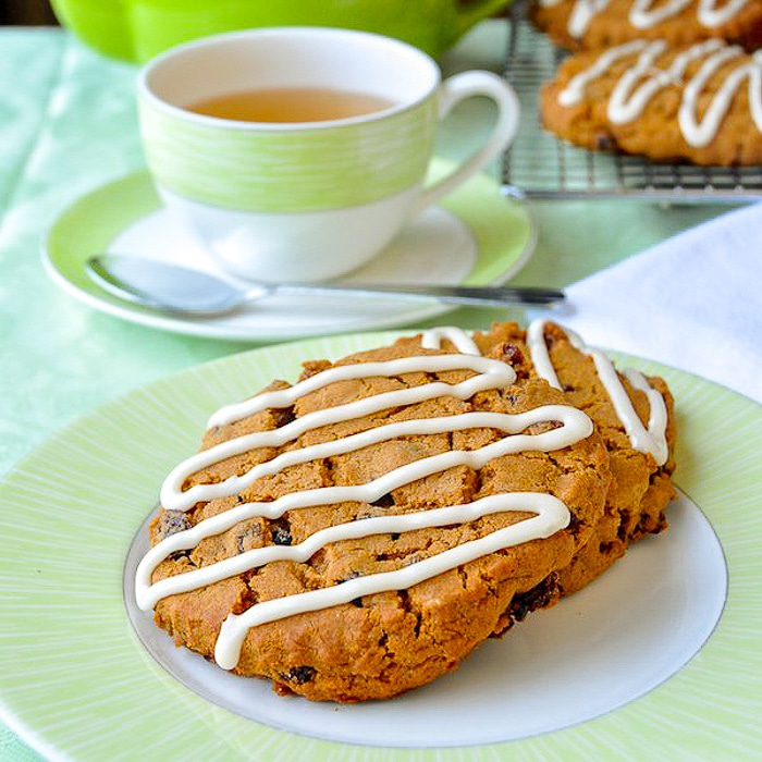Molasses Raisin Biscuit Cookies shown on a green and white plate with tea in background