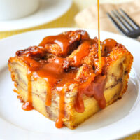 One serving of Cinnamon Roll Bread Pudding with caramel sauce on a white plate