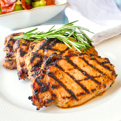 Rosemary Dijon Grilled Pork Chops close up photo on a white plate for featured image