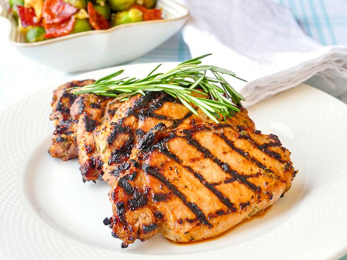 Rosemary Dijon Grilled Pork Chops shown with fresh rosemary sprig