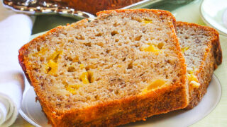 Close up photo of 2 slices of Mango Spice Banana Bread on a green plate