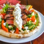 Soulaki Steak shown served with Greek salad on homemade flatbread.