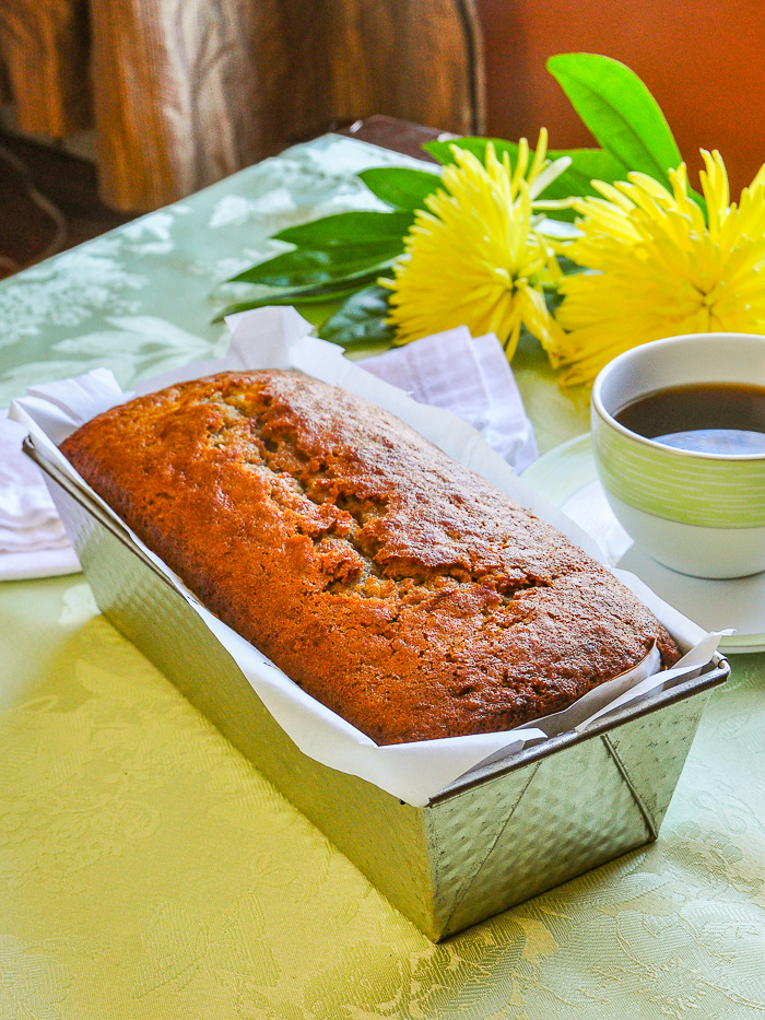 photo of Mango Spice Banana Bread still in the pn with coffee and flowers in the background