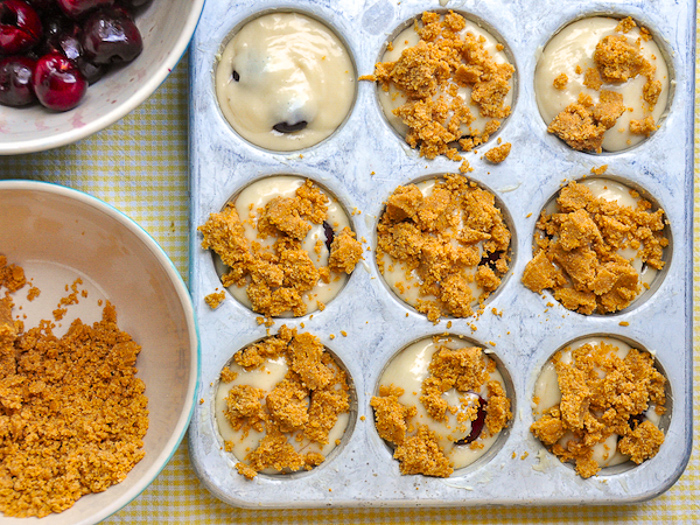 Adding the crumb topping to the cherry muffins
