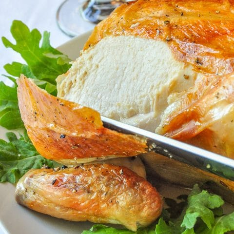 Asian Spice Brined Roast Chicken close up photo of juicy chicken breast being carved