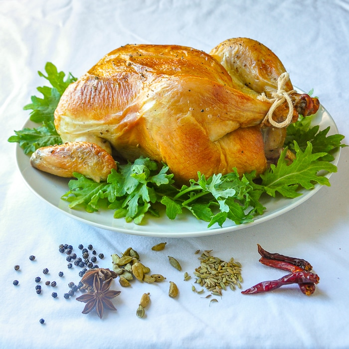 Uncarved Asian Spice Brined Roast Chicken surrounded by the spices used in the recipe