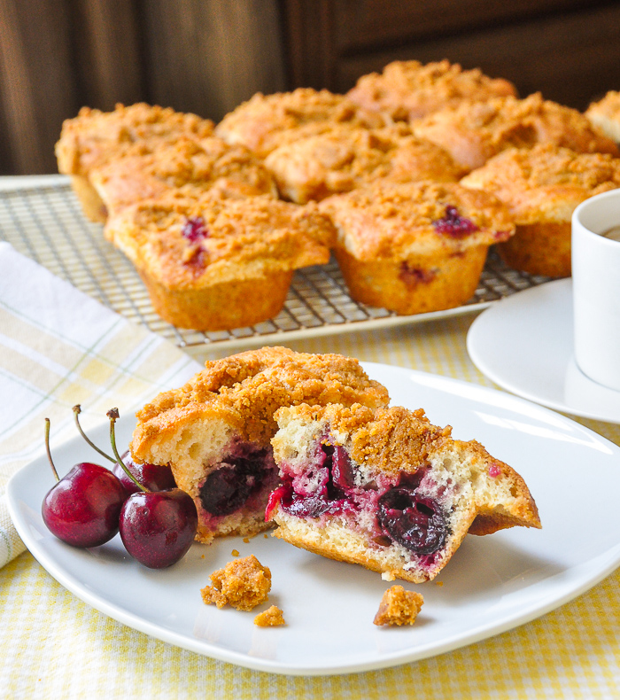 Wide shot photo of cherry muffins split in half to reveal the whole cherries inside