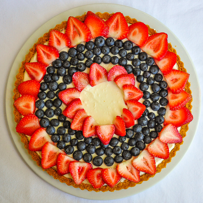 Photo of an uncut No Bake White Chocolate Cheesecake Tart on a white serving plate