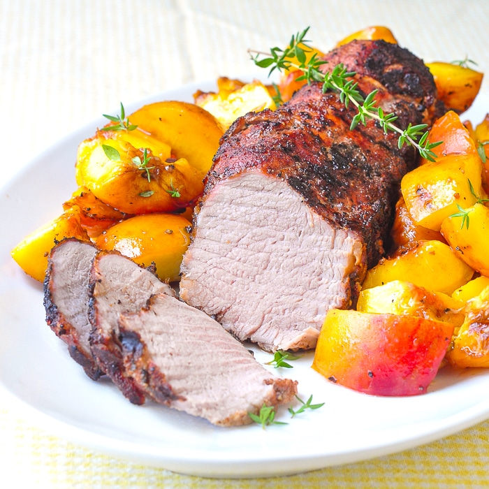 Grilled Balsamic Peach Pork Tenderloin shown sliced on a white serving platter