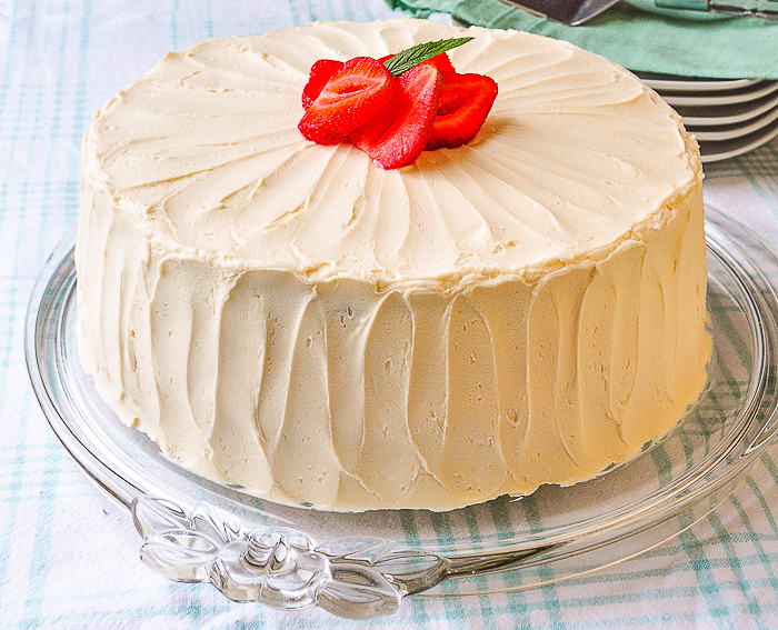 Strawberry Vanilla Butter Cake shown as a full uncut cake on a glass cake plate