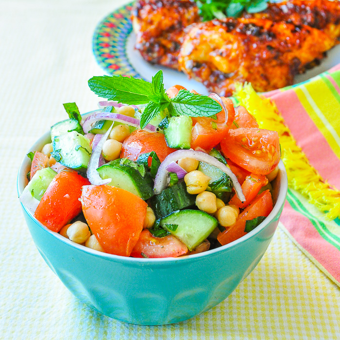 Tomato Cucumber Salad with Chickpeas & Mint shown in blue bowl with BBQ chicken in the background