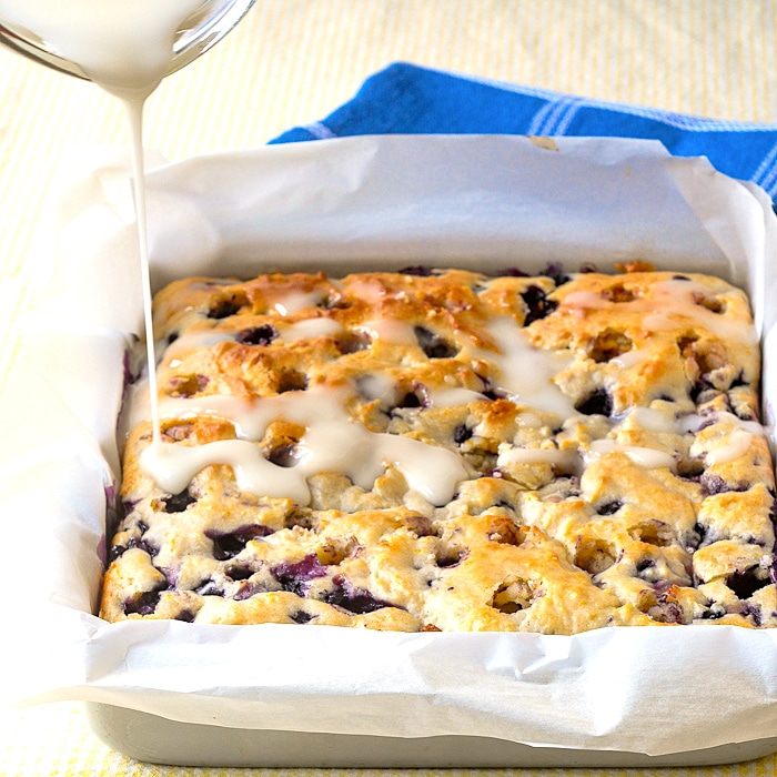 Photo of lemon glaze being poured onto Blueberry Lemon Drizzle Cake