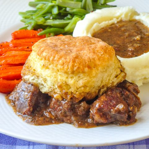 Braised Beef Pot Pie with Biscuit Topping close up photo of single serving on a white plate