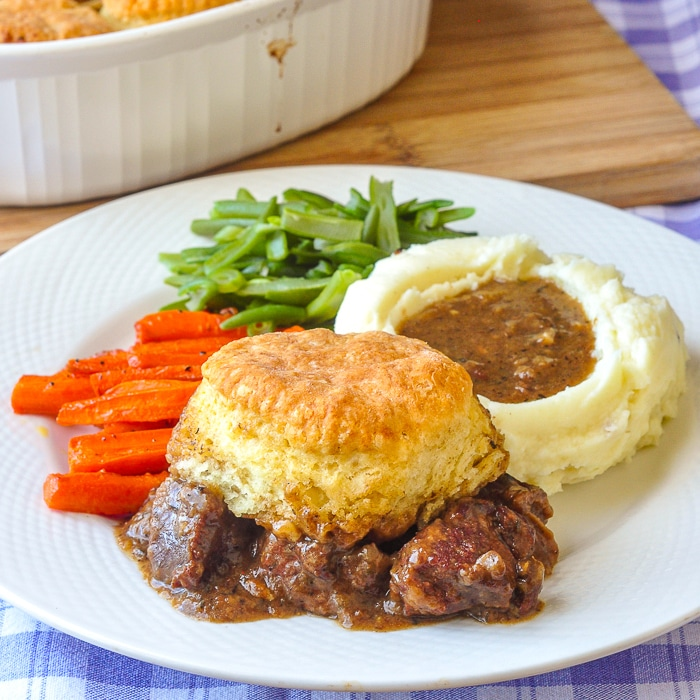 Braised Beef Pot Pie with Biscuit Topping wide shot of single serving on a white plate