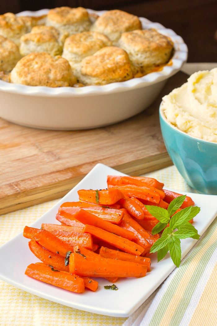 Honey Roasted Carrots with mint shown with mashed potatoes and pot pie in the background