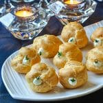 Garlic Thyme Cheese Puffs. close up shot on white serving plate.