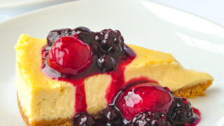 Close up photo of one slice of Bumbleberry Vanilla flan on a white plate