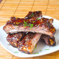 Honey Garlic Sticky Ribs stacked on a white plate